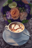 Coffee with foam and heart. Porcelain cup with coffee on the background of the bride's bouquet stock photos