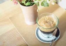 Coffee. Foam on Top of Coffee with Milk in The Glass with Spoon and Flower in The Vase on Wooden Table for Breakfast in The Morning royalty free stock image