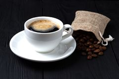 Coffee with foam in a white cup and a bag of grains on a black background. Stock Photos