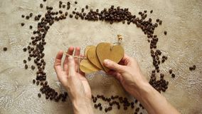 Coffee frame. Coffee background for coffee lovers. Rectangular frame from roasted coffee beans, with copy space inside. Hands put wooden hearts on each side stock video
