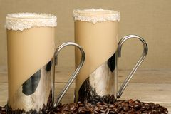Coffee frappe. Two mugs of iced coffee frappe with coffee beans on a wooden table royalty free stock photo