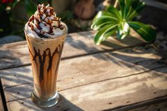 Coffee frappe with whipped cream on old wooden table in the morning sun stock photo