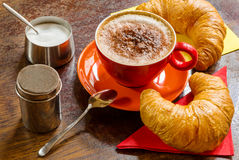 Coffee with frothed milk, cocoa and croissants. A tasty french breakfast composition in a restaurant Stock Images