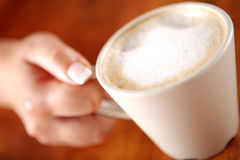 Coffee with frothed milk in hand (shallow Dof) Royalty Free Stock Photos