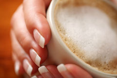 Coffee with frothed milk in hands (shallow Dof) Royalty Free Stock Photography