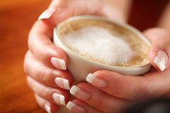 Coffee with frothed milk in hands (shallow Dof) Royalty Free Stock Images