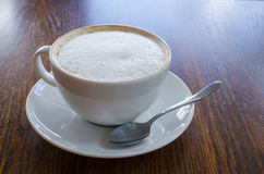Coffee with frothed milk in white cup. A simple coffee scene in a cafe during day time using natural lighting Royalty Free Stock Photo