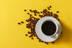 Hot cup of coffee with scattered beans on a yellow background stock photos