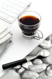 Coffee in glas cup with stylish napkin. Coffee in glass cup with stylish napkin with stones, silver teaspoon, keyboard, pen and newspaper stock photography