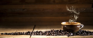 Coffee. Glass coffee cup and coffee beans on old wooden background