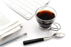 Coffee in glass cup with teaspoon. Pen, newspaper and keyboard on white background stock photo