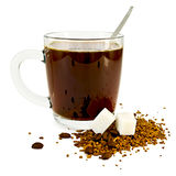Coffee in a glass mug with sugar. Coffee in a glass mug, a spoon, grains and granules of coffee on a table with two lumps of sugar with a light shade on white Royalty Free Stock Images