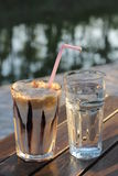 Coffee and a glass of water. Nes coffee and a glass of water next to the river Stock Images