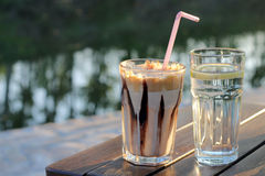 Coffee and a glass of water. Nes coffee and a glass of water next to the river Stock Photos