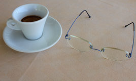 Coffee and glasses. A cup of coffee and a pair of glasses Royalty Free Stock Photo