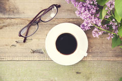 Coffee,glasses and lilac. Coffee cup,glasses and lilac flowers on wooden table Stock Photography