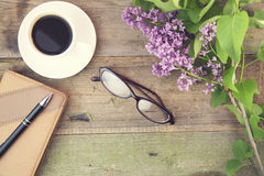 Coffee,glasses and lilac. Coffee cup,glasses and lilac flowers on wooden table Royalty Free Stock Photos