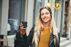Coffee on the go. Beautiful young blonde woman holding coffee cup and smiling while walking along the street. Stock Images