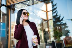 Coffee on the go. Stylish and young woman in coat drinking coffee outdoors. Beautiful hipster girl in modern urban. Outfit walking city streets with paper cup royalty free stock photos