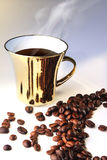 Coffee gold cup. Gold cup of coffee and coffee grain Stock Image