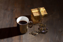 Coffee in golden cup with gift Royalty Free Stock Images