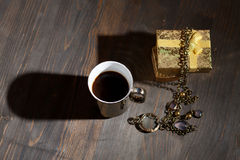 Coffee in golden cup with gift Royalty Free Stock Photos