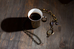 Coffee in golden cup with necklace Stock Image