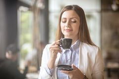 This coffee is so good break. Business woman standing in office drinking coffee stock photo