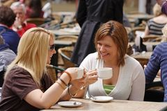 Coffee and good company. Two friends enjoying coffee in the sunshine stock image