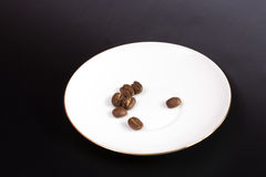 Coffee grain. On a round white plate on a black background Stock Images