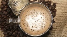 Coffee grains around the glass cup of cappuccino and a glass of water on sacking stock video
