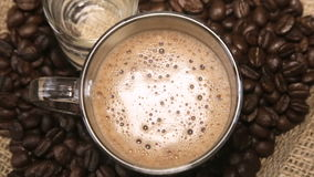 Coffee grains around the glass cup of cappuccino and a glass of water on sacking. Full hd video stock video