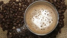 Coffee grains around the glass cup with cappuccino on sacking. The rotation of a circle stock footage