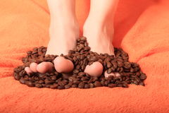 Coffee grains. Bare feet of little kid - girl covered with coffee grains Stock Photo