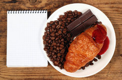 Coffee grains chocolate bars and croissant on white plate. Beside the small notebook Royalty Free Stock Photography