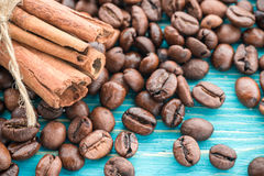 Coffee grains and cinnamon sticks on a wooden background royalty free stock photos