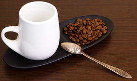 Coffee grains with a coffee in white cup Stock Photography