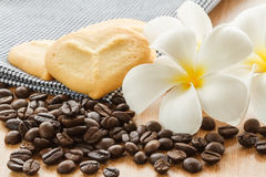 Coffee grains with cookie and plumeria flower Royalty Free Stock Images