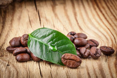 Coffee grains and green leaf Royalty Free Stock Photos