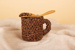 Coffee grains in spoon and cup Royalty Free Stock Photos