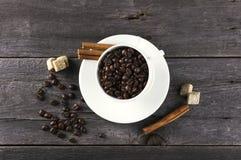 Coffee grains, sugar, cinnamon on dark wooden background Royalty Free Stock Photo
