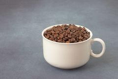 Coffee grains in a white cup. On a beautiful background stock photography