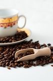 Coffee grains, wooden spoon and white cup Royalty Free Stock Photo