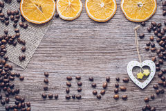 Coffee grains on a wooden surface with dried oranges and a wooden heart Royalty Free Stock Photo