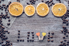 Coffee grains on a wooden surface with dried oranges and a wooden heart Stock Images