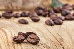 Coffee grains on wooden table Royalty Free Stock Photos