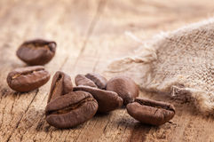 Coffee grains on wooden table Royalty Free Stock Images