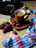 Coffee and grapes on a wooden table Royalty Free Stock Photo