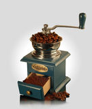 Coffee grinder. An antique coffee grinder machine on a white surface Royalty Free Stock Photo