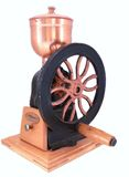Coffee grinder. An old antique coffee grinder with hand wheel over white Stock Image